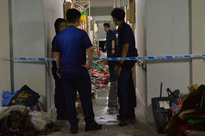Police officers standing outside the flat of a man who set his own apartment on fire after attacking two of his neighbours with a parang. -- ST PHOTO: ALPHONSUS CHERN