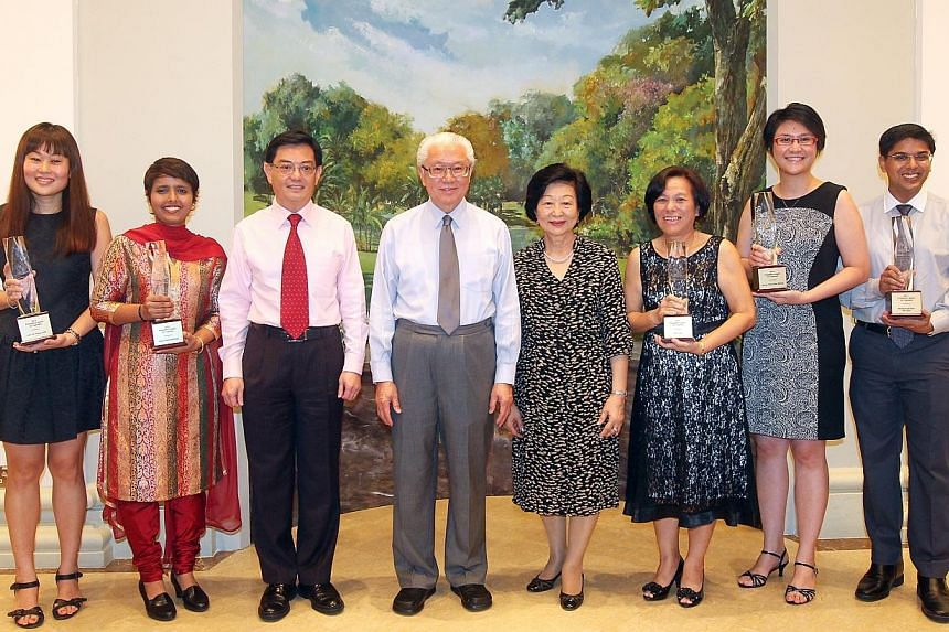President Tony Tan Keng Yam (fourth from left) with his wife Mary (fourth from right) and Education Minister Heng Swee Keat (third from left) standing with President's Award for Teachers 2014 winners (from left) Linda Lim, Rezia Rahumathullah, Sim Lu