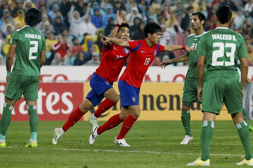 South Korea's Kim Young-Gwon (no. 19) celebrates with teammate Lee Jeong-Hyeop after scoring the second goal against Iraq during their Asian Cup semi-final football match at the Stadium Australia in Sydney on Jan 26, 2015.-- PHOTO: REUTERS