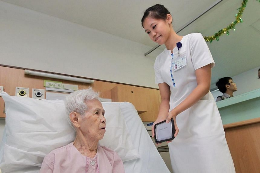 Changi General Hospital staff nurse Sheree Ye (right), using the iCOM translation app to communicate with patient Kan Wan Sin on July 25, 2014. Language translation apps, driverless cars that park themselves and technology that aids home rehabilitati