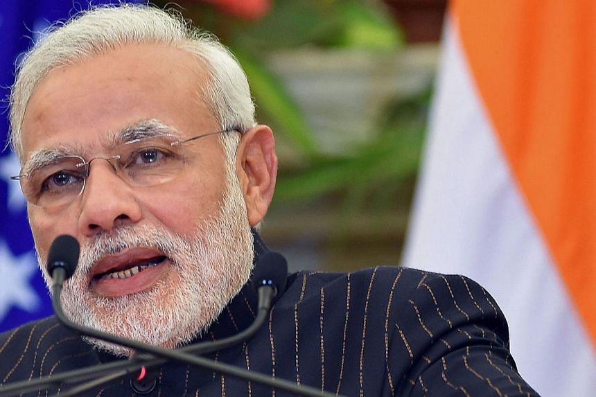 Indian Prime Minister Narendra Modi speaks during a joint press conference after delegation level talks with US President Barack Obama in New Delhi on Jan 25, 2015.The Indian PM turned out in a dark pinstripe suit embroidered with his own name