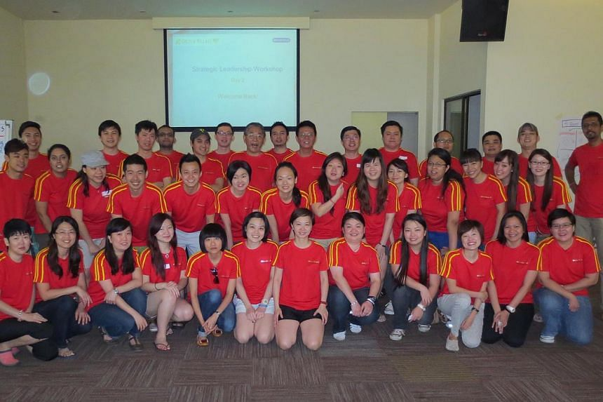 Ms Cheo (above, front row, seventh from left) at a Golden Village strategic workshop in 2013. -- PHOTO: COURTESY OF CLARA CHEO