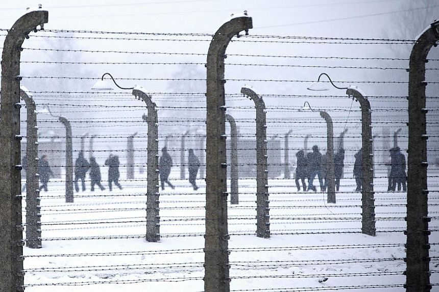Visitors walk inside former Nazi concentration camp Auschwitz-Birkenau in Oswiecim, Poland on Jan 25, 2015, days before the 70th anniversary of the liberation of the camp by Russian forces. -- PHOTO: AFP