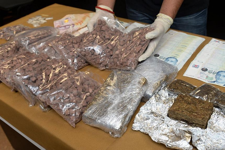 Drugs and over $12,000 cash found during a raid on an alleged drug syndicate by Central Narcotics Bureau in September 2014. -- PHOTO: ST FILE