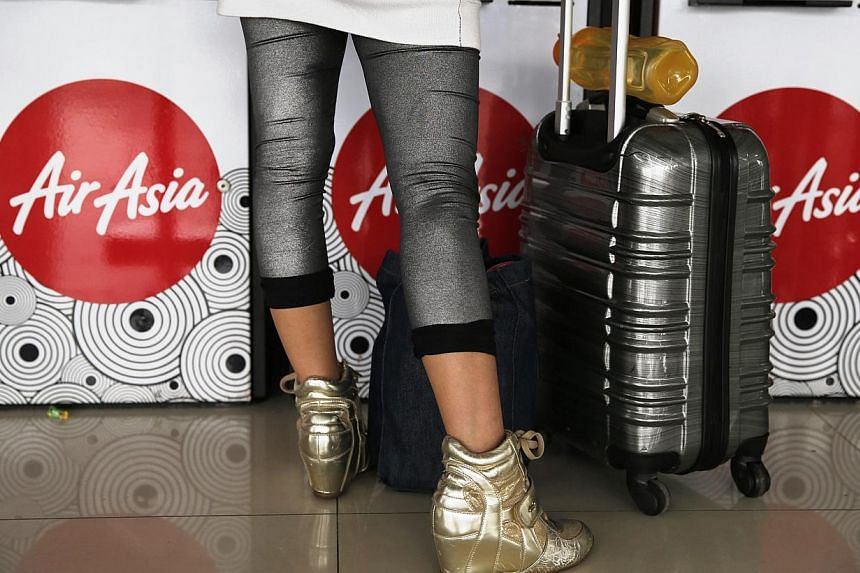 A woman standing in front of an AirAsia check-in machine at Soekarno Hatta airport in Jakarta, on Jan 21, 2015.AirAsia, in a posting on Facebook, has said that it will be abolishing is fuel surcharge from Monday.The move will be implement
