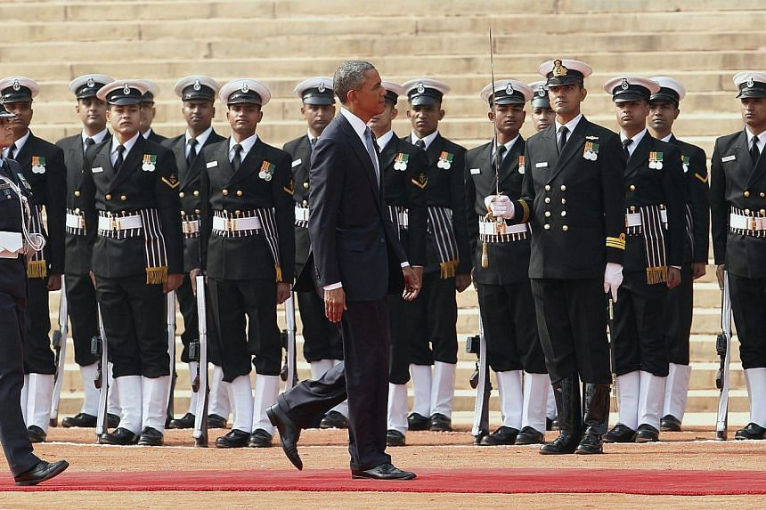 US President Barack Obama (centre) walks on a red carpet as he inspects a guard of honor during his welcoming ceremony at the Indian president's house in New Delhi, India, on Jan 25, 2015. -- PHOTO: EPA