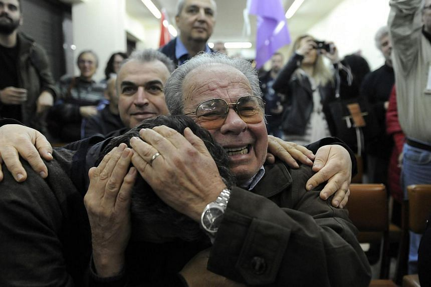 Supporters of opposition leader and head of radical leftist Syriza party Alexis Tsipras cheer at exit poll results in the northern port city of Thessaloniki Sunday. -- PHOTO: REUTERS