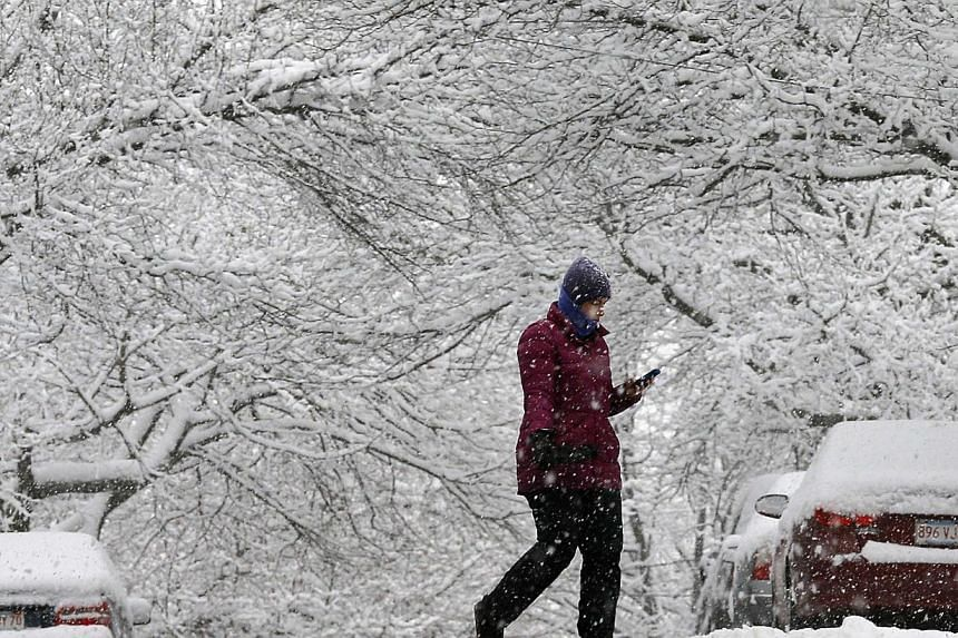 A woman crosses a road during a winter snowstorm in Somerville, Massachusetts over the weekend. The US Northeast, including New York and Boston, is bracing for a  snowstorm that may be of historic proportions starting today, the National Weather