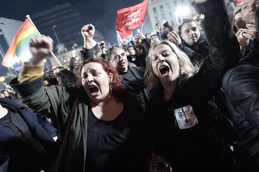 Anti-austerity Syriza party supporters celebrating as leader Alexis Tsipras speaks folllowing victory in the election in Athens on Jan 25, 2015. -- PHOTO: AFP