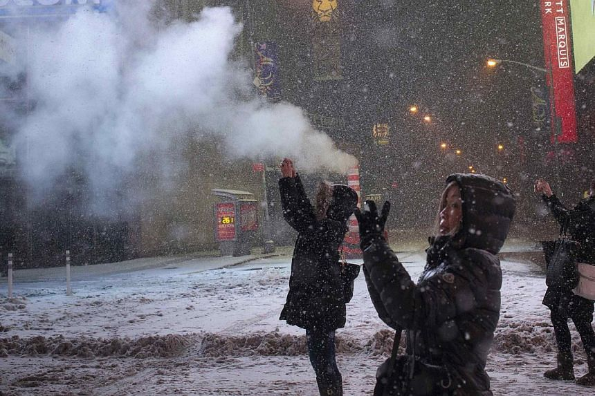 Female tourists use their smart phones to capture a snow storm in Times Square, New York early morning on Jan 27, 2015. -- PHOTO: REUTERS