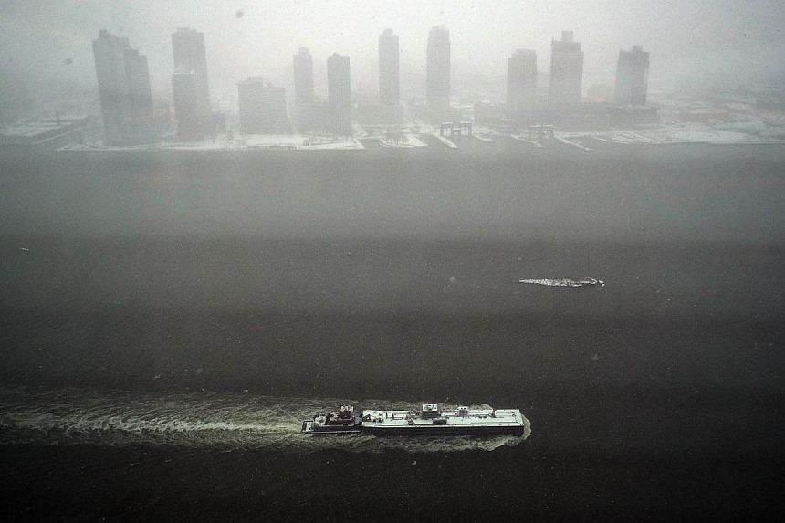 A tugboat sails on the East River during a snow storm in New York on Jan 26, 2015. -- PHOTO: AFP