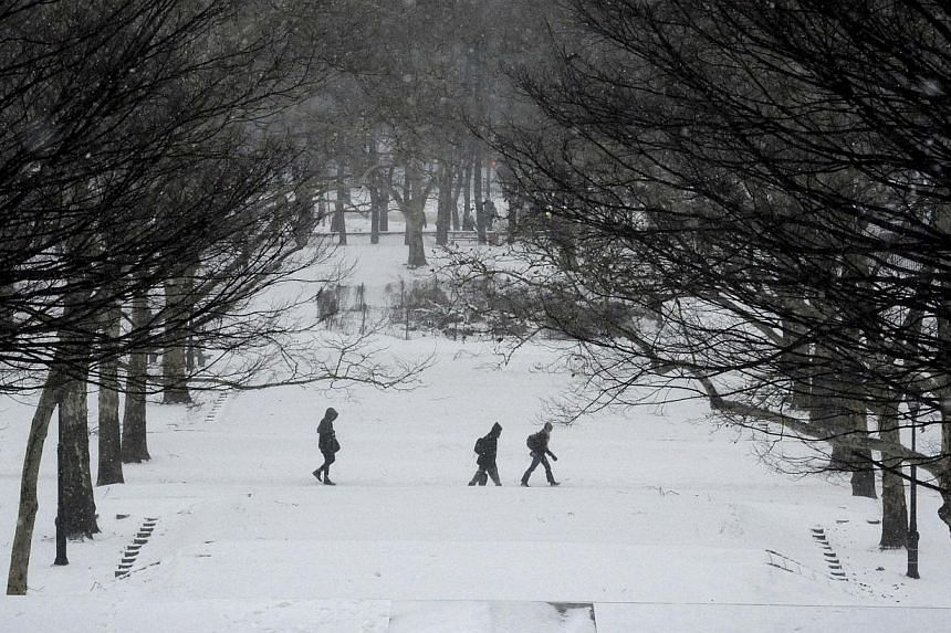 People walk in falling snow in Fort Greene Park in the Brooklyn borough Brooklyn in New York City on Jan 26, 2015. -- PHOTO: REUTERS