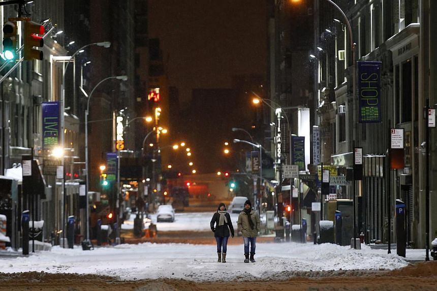 People walk on a snow covered West 38th street in midtown Manhattan in New York City early on Jan 27, 2015. -- PHOTO: REUTERS