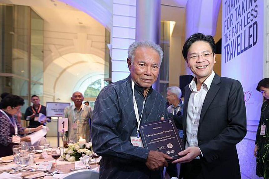 Poet Edwin Nadason Thumboo (left) receiving a memento from Minister for Culture, Community and YouthLawrence Wong.-- ST PHOTO: ONG WEE JIN