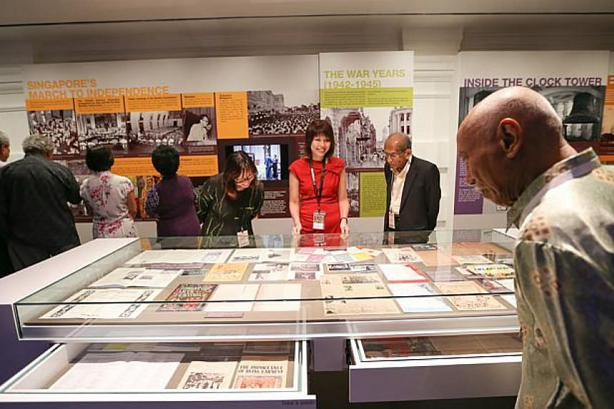 Members of the pioneer generation viewing the newly launched Heritage Gallery.-- ST PHOTO: ONG WEE JIN
