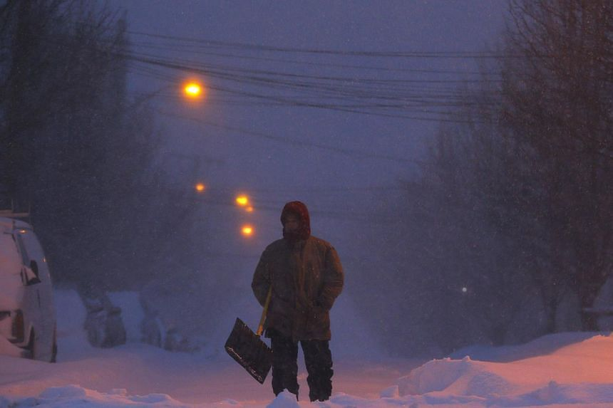 A man with a snow shovel stands in the middle of a snow covered street during a large winter blizzard in Somerville, Massachusetts on Jan 27, 2015. -- PHOTO: REUTERS