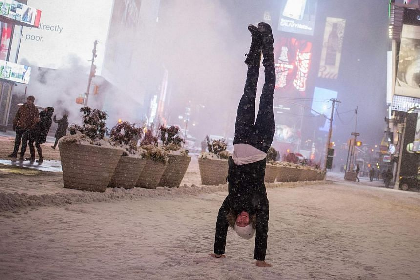 Jamina Goop, from Liechtenstein, does a handstand as she is photographed by a friend (unseen) during a snow storm in Times Square, New York early morning on Jan 27, 2015. -- PHOTO: REUTERS