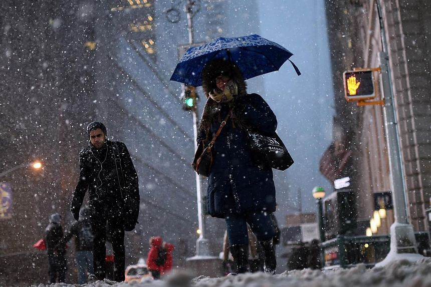 Commuters make their way in New York's Times Square during a snow storm on Jan 26, 2015. -- PHOTO: AFP