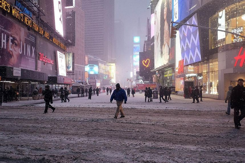 People cross a street covered in snow in New York's Times Square during a snow storm on Jan 26, 2015. -- PHOTO: AFP