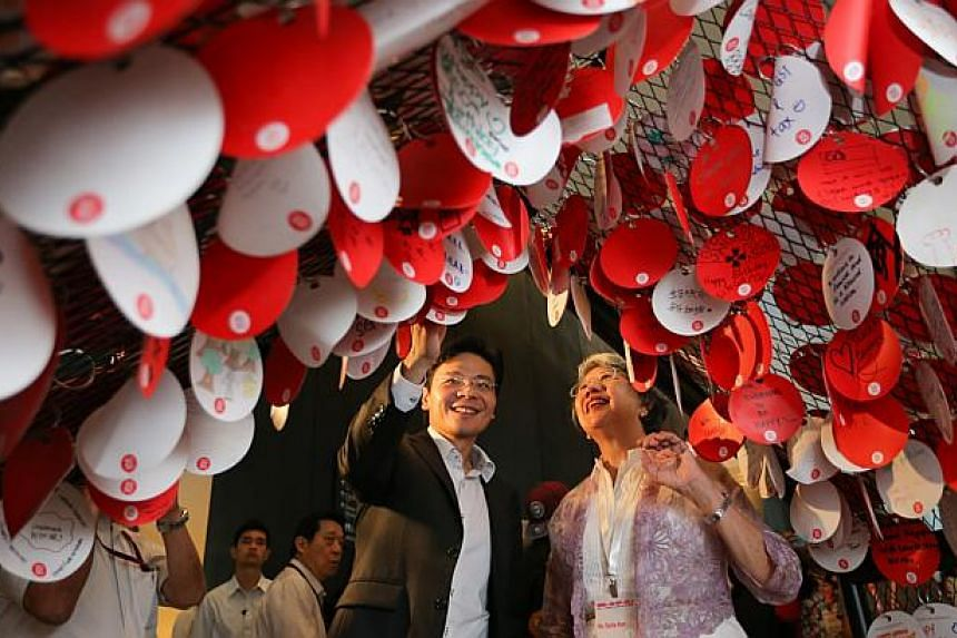 Minister for Culture, Community and Youth Lawrence Wong (left) and Ms Stella Kon (right), a playwright of the pioneer generation, together hanging up her written wish for Singapore.-- ST PHOTO: ONG WEE JIN