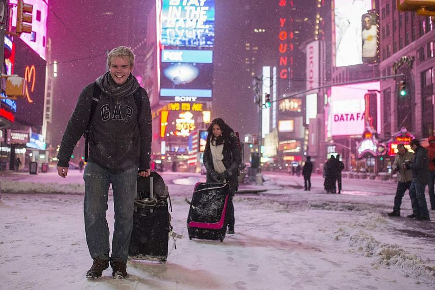 Alexander Valeur of Denmark and Katia Borredo from Mexico carry their baggage through a snowstorm in Times Square, New York early morning on Jan 27, 2015. -- PHOTO: REUTERS