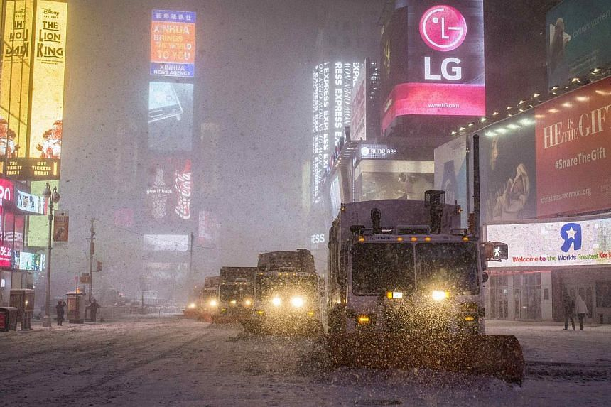 Snow plow trucks clear the roads during a snowstorm in Times Square, New York early morning on Jan 27, 2015. -- PHOTO: REUTERS