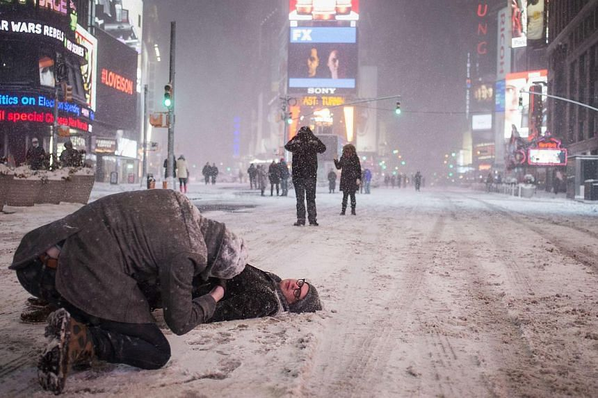 Manhattan resident Jerry Risner lies in the middle of 7th Ave as his friend P.J. Chernick takes a photo during a snow storm in Times Square, New York early morning on Jan 27, 2015. -- PHOTO: REUTERS
