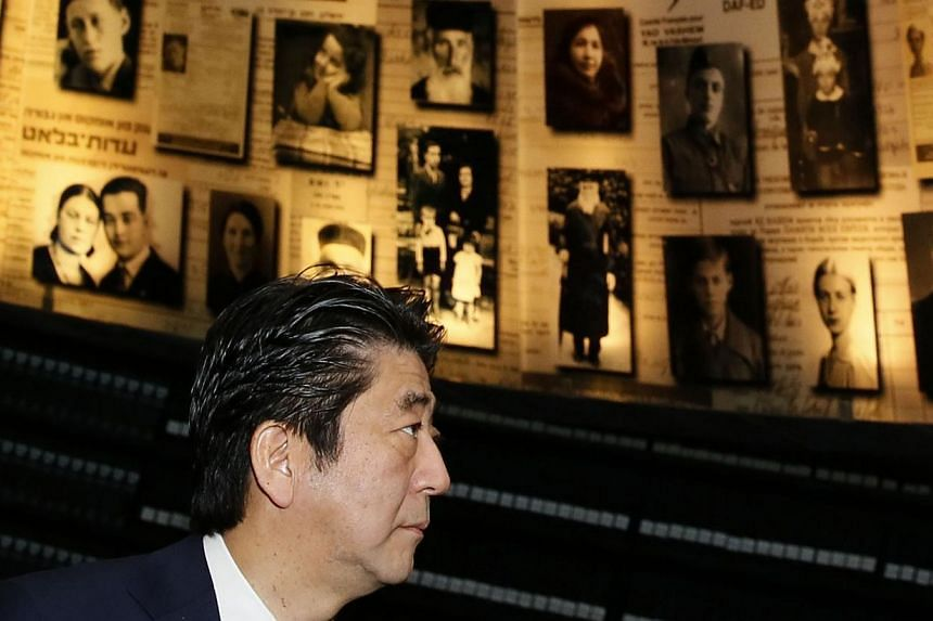 Japanese Prime Minister Shinzo Abe looks at pictures of Jewish Holocaust victims at the Hall of Names on Jan 19, 2015 during their visit to the Yad Vashem Holocaust Memorial museum in Jerusalem commemorating the six million Jews killed by the Nazis d