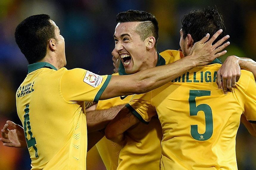 Australia's Jason Davidson celebrating his goal with Mark Milligan and Tim Cahill during the Semi Final Asian Cup match between Australia and the United Arab Emirates at Hunter Stadium in Newcastle, Australia, on 27 Jan 2015. First-half goals from de