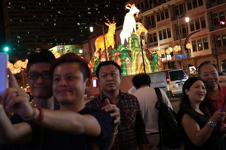 Members of the public taking selfies against the backdrop of the 10m-high centerpiece of the Chinatown street light-up, which sees three majestic goats perched on top a cliff. Chinatown will come alight this Saturday with 338 goat-shaped lanterns in
