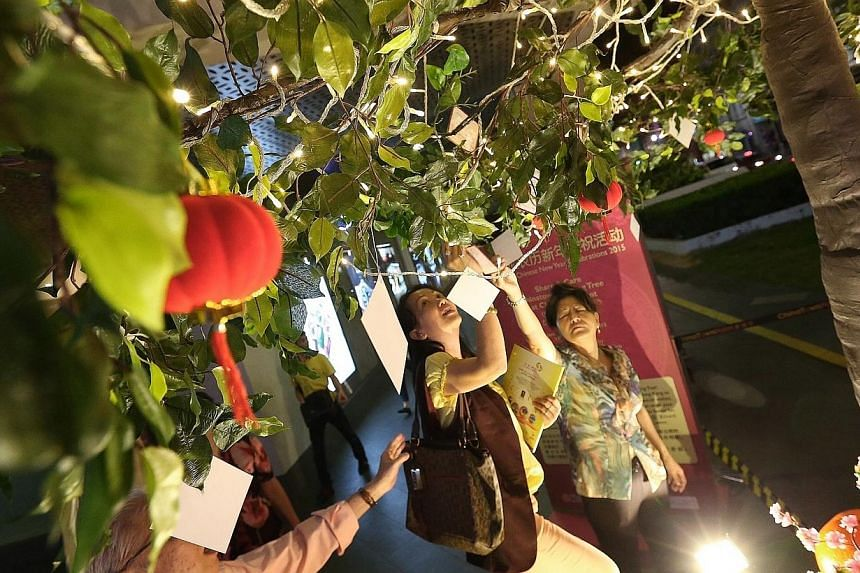 Visitors leaving their wishes on the Chinatown Wishing Tree outside Chinatown Point. Chinatown will come alight this Saturday with 338 goat-shaped lanterns in anticipation of the Chinese New Year celebrations. -- ST PHOTO: NEO XIAOBIN
