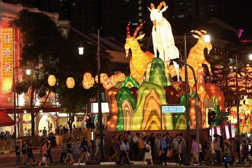 Members of the public seen against the backdrop of the 10m-high centerpiece of the Chinatown street lightup which features three goat lanterns. Chinatown will come alight this Saturday with 338 goat-shaped lanterns in anticipation of the Chinese