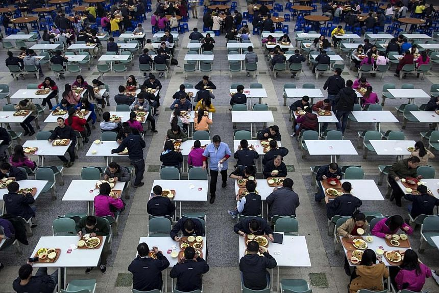 Workers eating their lunch at a restaurant inside a Foxconn factory in the township of Longhua in Shenzhen, Guangdong province on Jan 21, 2015. -- PHOTO: REUTERS