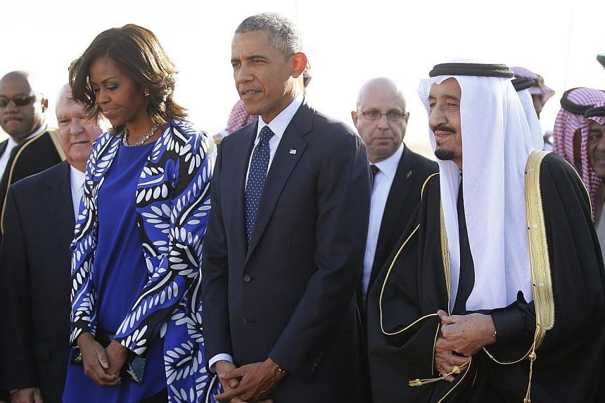 US President Barack Obama and first lady Michelle Obama are greeted by Saudi Arabia's King Salman (right) as they arrive at King Khalid International Airport in Riyadh, on Jan 27, 2015.US President Barack Obama landed in Saudi Arabia on Tuesday