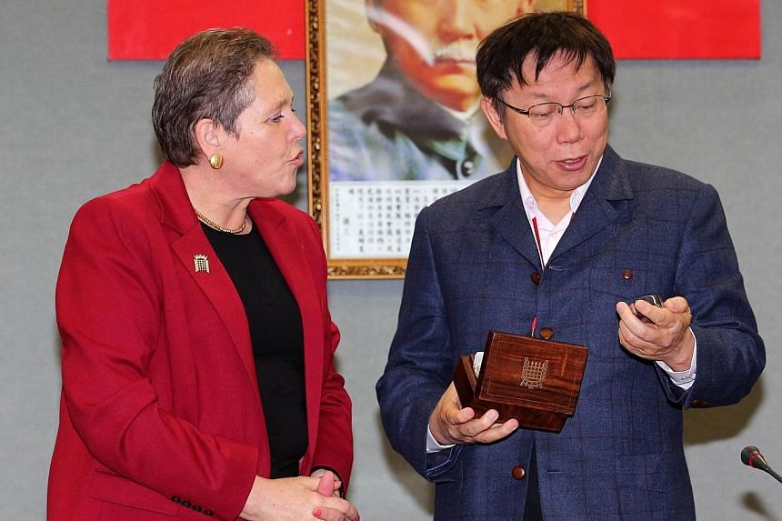 Taipei Mayor Ko Wen-je (rght) receiving a gift of a watch from visiting British Transport Minister Baroness Susan Kramer on Jan 26, 2015. Mr Ko apologised for joking he would send the watch for scrap. -- PHOTO: AFP