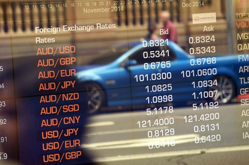 Australian Securities Exchange boards showing the local dollar in Sydney on Dec 8, 2014. Many of UBS' wealthiest Asian clients have begun to abandon the Australian dollar as the country's bond yield premium over the US' slid and the Federal Reserve d
