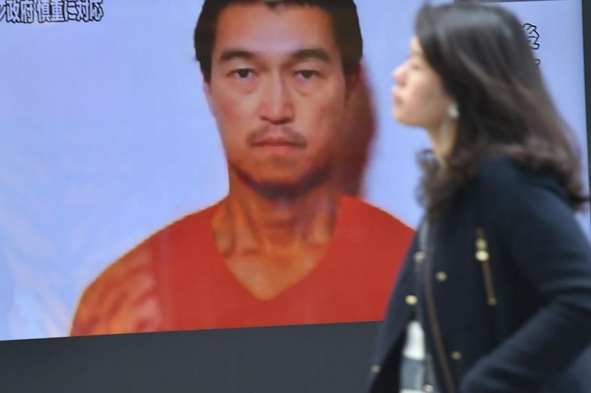 A pedestrian walks past a TV screen in Tokyo on Jan 26, 2015 showing news reports about Japanese journalist Kenji Goto being held by Islamic militants. Japan is working with Jordan to free both Goto and a Jordanian pilot, officials said on Tuesday, d
