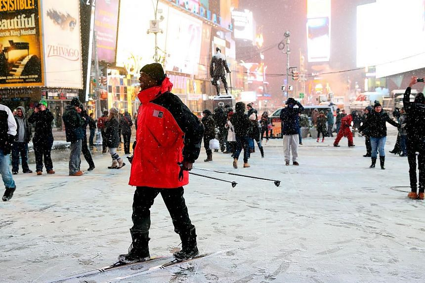 A man stands on skis in Times Square in New York City on Jan 26, 2015. -- PHOTO: AFP