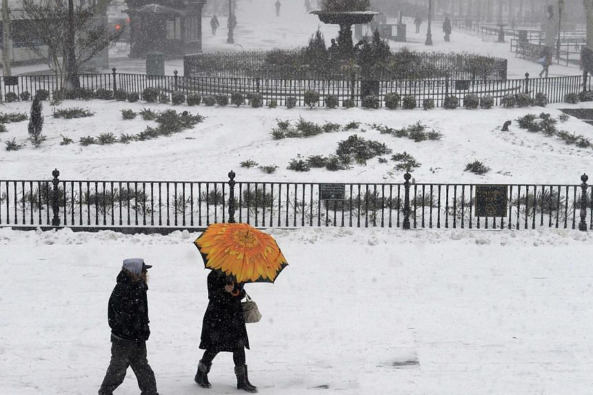 People walk in the Borough Hall section of downtown Brooklyn in New York City in falling snow on Jan 26, 2015. -- PHOTO: REUTERS