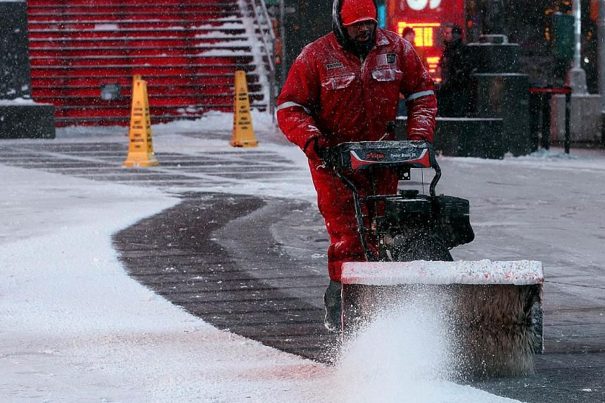 A man uses a snow thrower in Times Square in New York City on Jan 26, 2015. -- PHOTO: AFP