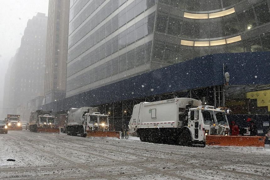 A New York Department of Sanitation snow truck plows the streets as a bike rides by during a winter storm in New York on Jan 26, 2015. -- PHOTO: EPA