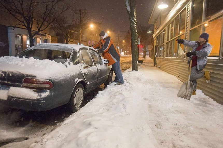 An employee of a local restaurant clears his car of snow to make return home as a statewide travel ban goes into effect in New Haven, Connecticut on Jan 26, 2015. -- PHOTO: REUTERS