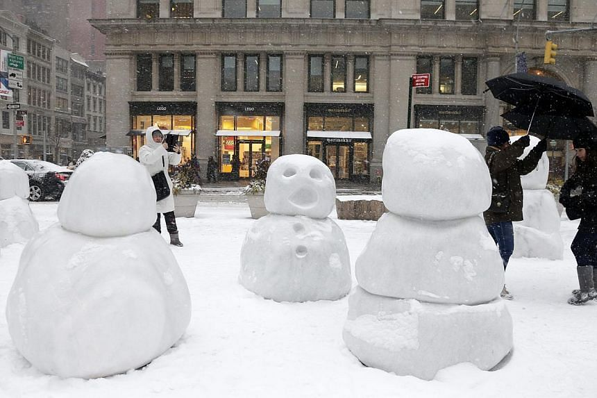 People walk past and take pictures of Swiss artist Peter Regli Reality Hacking No. 320 'Snow Monsters 2015' during a winter storm in New York on Jan 26, 2015. -- PHOTO: EPA
