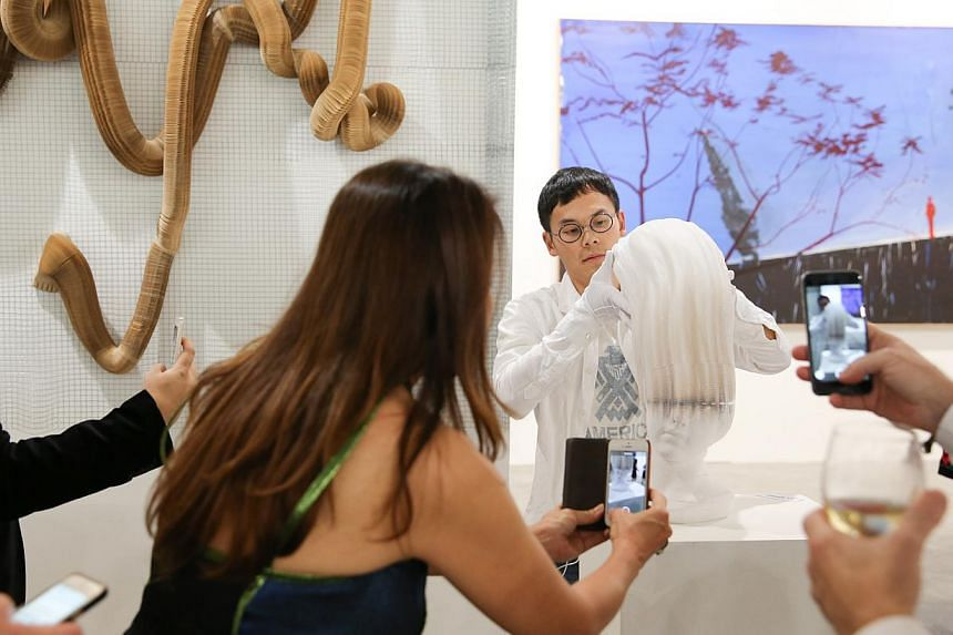 A gallerist with what looks like a bust (above), but is actually made of paper and can be stretched like a slinky tube. Huang Po-chih from Taiwan mixing an alcoholic lemon drink in his performance art. -- ST PHOTO: ONG WEE JIN