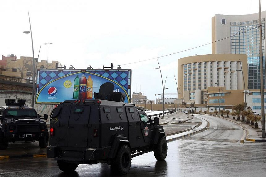 Libyan security forces and emergency services near the Corinthia Hotel (right) in Tripoli on Jan 27, 2015,after Islamic State in Iraq and Syria (ISIS) fighters said they staged an attack on it. -- PHOTO: AFP