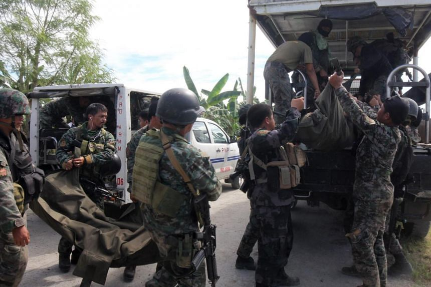 Members of elite Police Special Action Force carry bodies of their comrade who was killed in an encounter in the town of Mamasapano, Maguindanao province, Philippines, on Jan 26, 2015. -- PHOTO: EPA