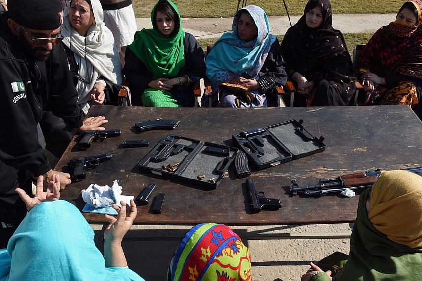 A Pakistani Anti Terrorist Squad (ATS) police official displays various types of firearms during a weapons training session for school, college and university teachers in Peshawar on Jan 27, 2015. -- PHOTO: AFP