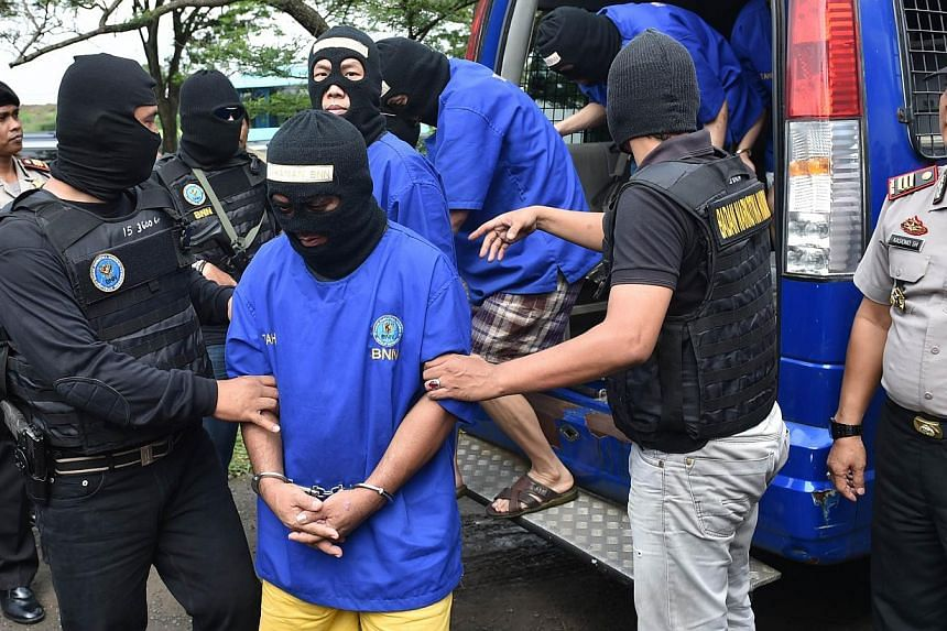 Arrested members of the international drug syndicates including major Hong Kong drug lord Wong Chi Ping (not pictured) wearing masks are escorted by police and agents of National Narcotics Agency to a ceremony to burn some of the 862kg of crystal met
