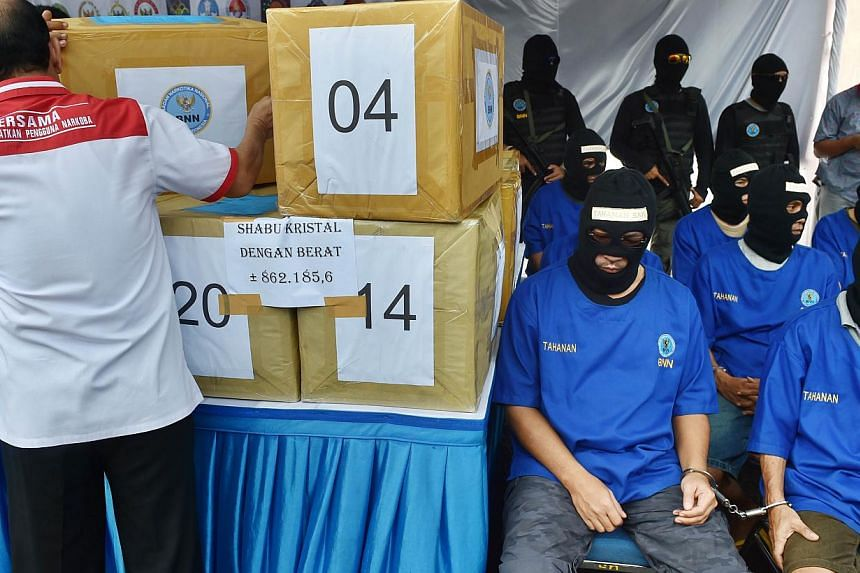 Arrested members of the international drug syndicate led by major Hong Kong drug lord Wong Chi Ping (front row, second right) wearing masks sit next to boxes containing some of the 862kg of crystal methamphetamine before they are destroyed by Nationa