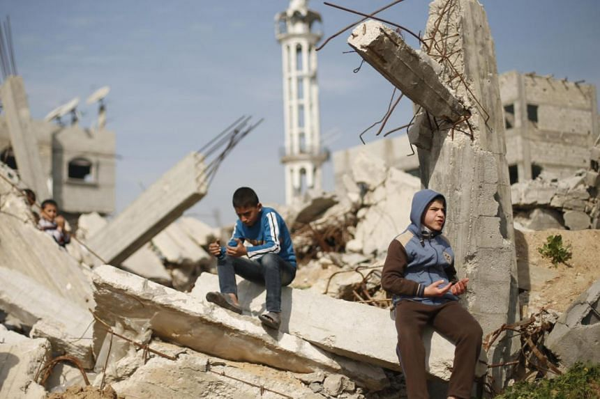 Palestinian boys attend Friday prayers as they sit at the remains of a house that witnesses said was destroyed by Israeli shelling during a 50-day war last summer, in the Shejaia neighbourhood east of Gaza City on Jan 23, 2015. -- PHOTO: REUTERS